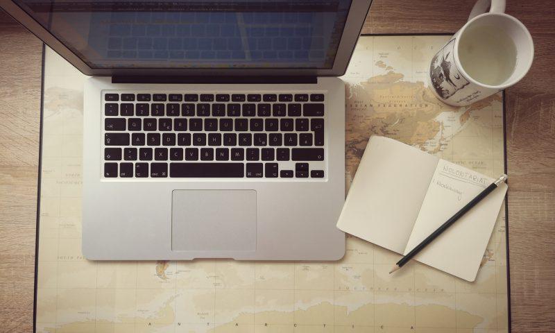 Laptop i notatnik. Poszukiwanie informacji na temat platformy Workaway