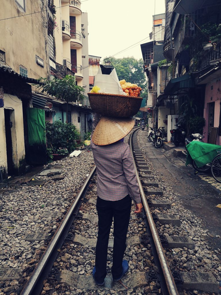 Atrakcje Hanoi. Życie wzdłuż torów kolejowych w Hanoi. Train street in Hanoi. Kobieta z koszykiem na głowie.