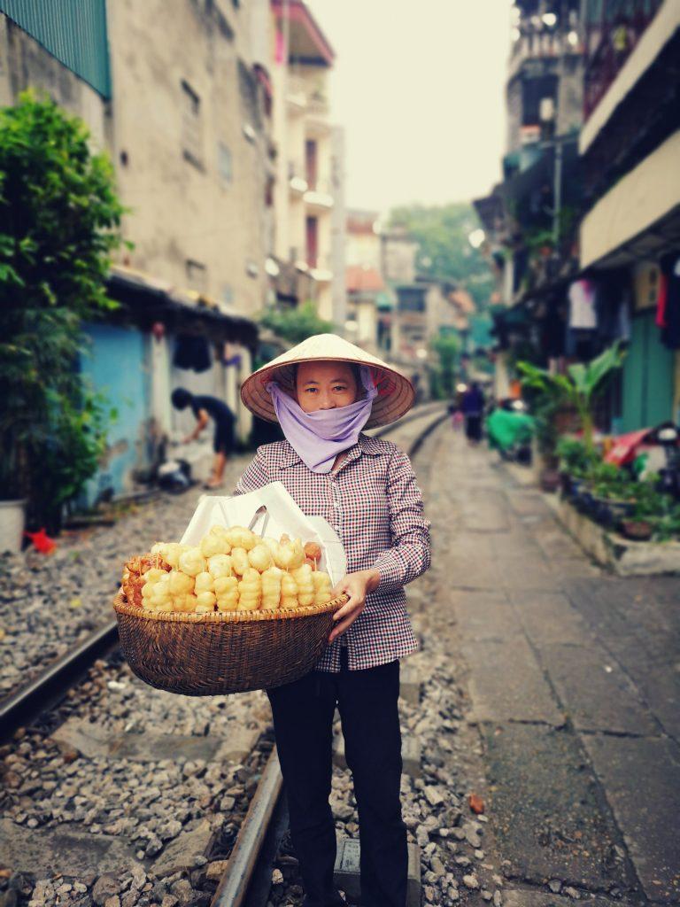 Mniej znane atrakcje Hanoi. Tory kolejowe w Hanoi i pociąg przejeżdżający tuż obok mieszkańców. Train street. Kobieta sprzedająca wypieki w Wietnamie.