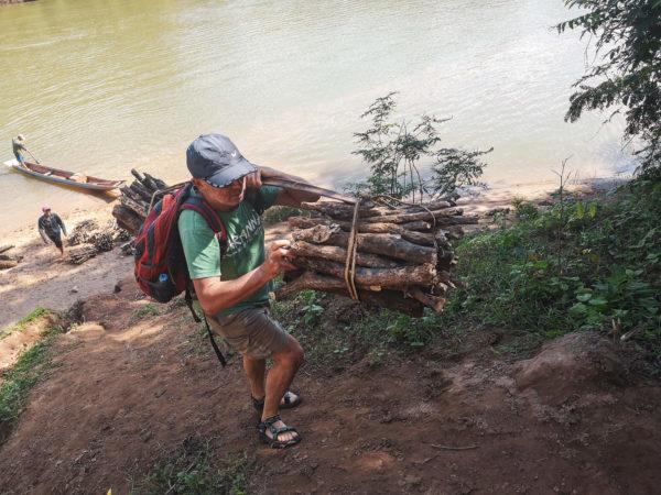 Praca w Laosie. Tradycyjne noszenie drewna w Laosie. Nad rzeką Mekong w Laosie