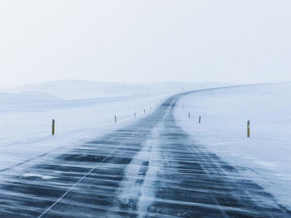 Zasypana śniegiem ulica. Zamieć śnieżna. Droga krajowa na Islandii w zimie